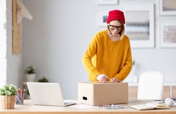 Cheerful female entrepreneur in stylish clothes and glasses smiling and writing address on carton box while sending order to customer at home