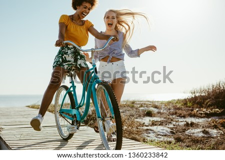Cheerful female friends having fun with a cycle outdoors. Two girls playing with a bicycle on the boardwalk on seaside.