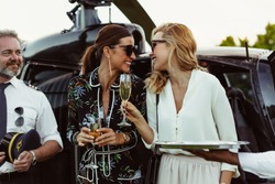 Cheerful female friends having wine outside a helicopter with pilot standing by. Women enjoying welcome drinks by a helicopter.