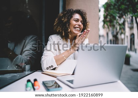 Cheerful female graphic designer feeling delight and happiness while doing remote work on laptop computer rejoicing at sidewalk cafe, joyful woman with netbook satisfied with freelance lifestyle Stock photo ©