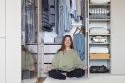 Cheerful female in lotus position at modern wardrobe storage. Happy housewife posing meditating at home closet full of clothing. Smiling woman relaxing after domestic cleaning housework