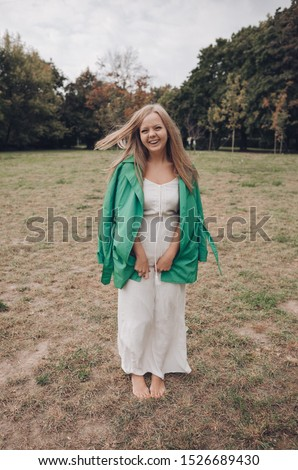 Cheerful female laugh. Young happy woman in a white dress and green trench coat walks in nature and laughs. #1526689430