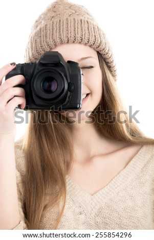 Cheerful female photographer wearing casual style clothes, smiling, taking pictures with digital camera, teenage girl hobby photography