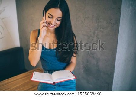 Cheerful female student with personal planner in hand standing indoors and making positive smartphone conversation, happy woman with textbook receiving cellphone call connected to 4g internet