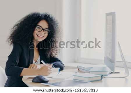 Cheerful female student writes down necessary information in notebook, makes notes, has glad expression, wears transparent glasses and black formal wear, sits at desktop with books and computer