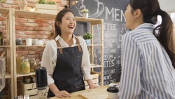 cheerful female waiter taking order from young female costumer standing at cafe counter. two laughing women friends meeting in coffee shop while one working as waitress. happy regular client indoors