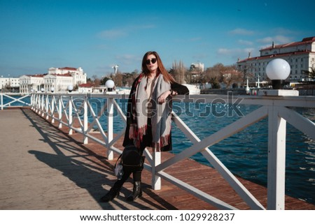 Cheerful female walking on city street enjoying free time on spring weekends, happy woman in sunglasses evokes sea fresh air #1029928237