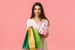 Cheerful feminine cute brunette woman holding shopping bags and wrapped gift, smiling, prepared surprise present for girlfriend, standing in dress over pink background happy