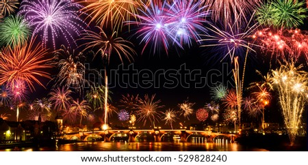 Cheerful fireworks display in the city, with lots of colorful bangs rising high into the night sky, with black copyspace #529828240