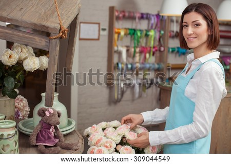 Cheerful florist is making a bouquet in her workshop. She is touching roses happily and smiling. The woman is looking at the camera with inspiration