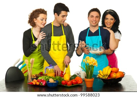 Cheerful four friends preparing dinner together in kitchen against white background