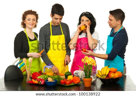 Cheerful four friends with colorful aprons cooking together in kitchen