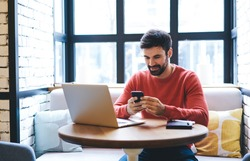 Cheerful freelancer with beard browsing smartphone and smiling while sitting at table with laptop and notebook in light cafe in daytime