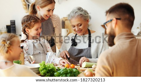 Cheerful friendly family gathering around kitchen table and preparing healthy food with fresh organic vegetables for weekend dinner at home  stock photo