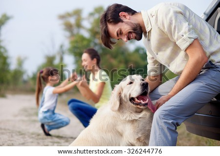 Cheerful friendly family is resting in park. The man is playing with dog and leaning on car. The mother and daughter are kneeling and holding hands. They are smiling