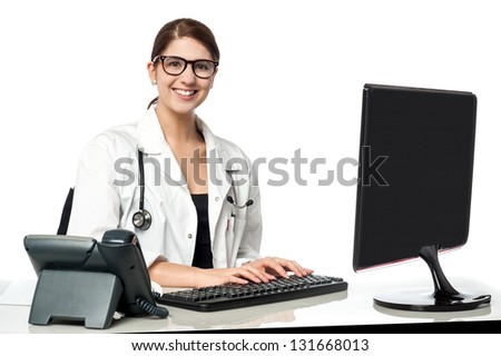 Cheerful friendly female doctor typing report.