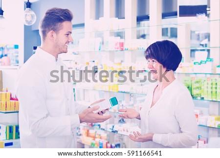 Cheerful friendly man pharmacist wearing white coat helping customers in drug store
