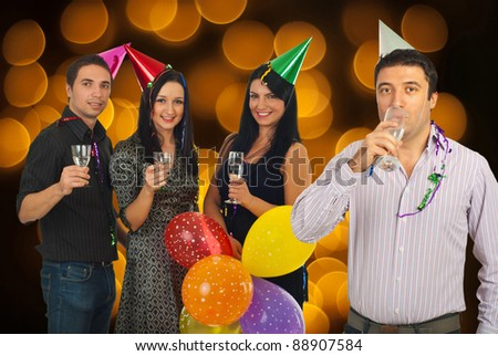 Cheerful friends celebrating New Year's Eve party and holding glasses with champagne over background with Christmas lights