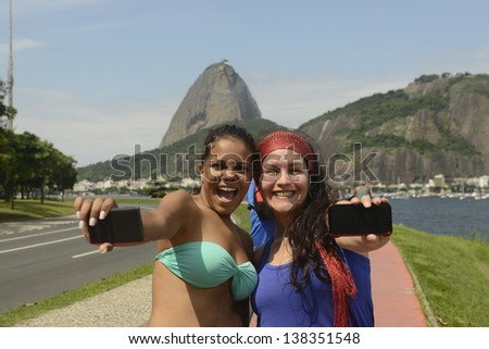 Cheerful friends multiethnic, photographing themselves with mobile phones across the Sugar Loaf in Rio de Janeiro, Brazil.