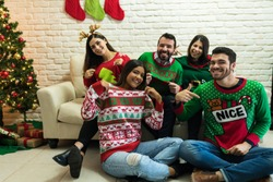 Cheerful friends showing off their ugly sweater while enjoying Christmas party at home
