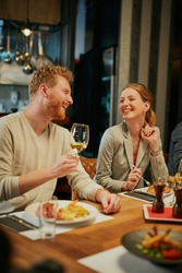 Cheerful friends sitting in restaurant for dinner, eating and drinking wine.