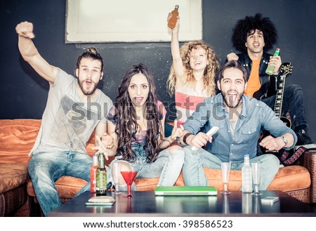 Cheerful friends sitting on the couch and exulting while watching a sport match on tv - Happy young cool people having fun at a home party