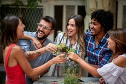 Cheerful friends taps with glasses and toasts with drink