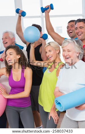 Cheerful friends with hands raised holding equipment in fitness studio