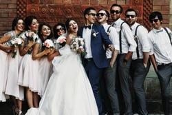 Cheerful & fun groom with bride, bridesmaids & groomsmen posing outdoors
