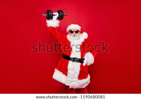 Cheerful funny trendy stylish fashionable strong sporty virile muscular Santa in eyeglasses gloves fur white red winter coat black belt lifting one big dumbbell striving isolated on red background