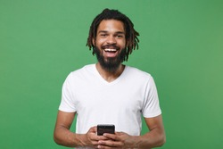 Cheerful funny young african american guy with dreadlocks 20s in white casual t-shirt posing using mobile cell phone typing sms message isolated on green color wall background studio portrait