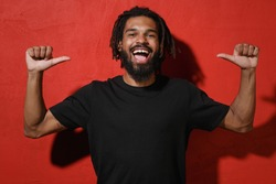 Cheerful funny young african american man with dreadlocks 20s wearing black casual t-shirt posing pointing thumbs on himself looking camera isolated on bright red color background studio portrait