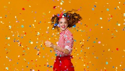 cheerful funny young woman with festive confetti on yellow background
