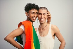 Cheerful gay couple with pride flag on white background. Two homosexual men standing together and smiling.
