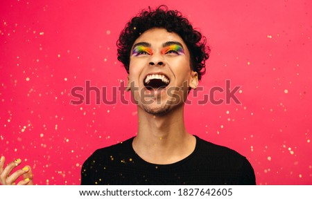 Cheerful gay man with glitters flying against red background. Excited young male with rainbow eye makeup throwing up the glitter and laughing. Сток-фото ©