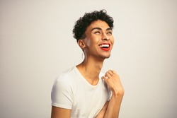 Cheerful gay man with make up on. Transgender male wearing red lip stick and earrings laughing on white background.