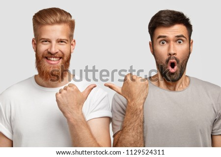 Cheerful ginger male in high spirit indicates at his companion with surprised expression, wear casual t shirts, express happiness and surprisement, isolated over white background. People and emotions