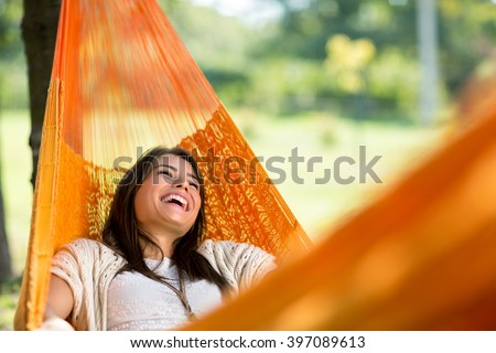 Cheerful girl enjoy in orange hammock outdoor #397089613