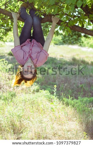 Cheerful girl hanging on a tree upside down