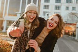 Cheerful girl in knitted hat walking with friend in city. Pleased ladies having fun in autumn.