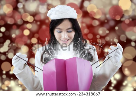 Cheerful girl looking at the shopping bags with miracle light, shot with light glitter background