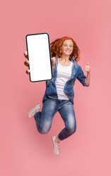 Cheerful girl redhead teenager jumping up, showing thumb up and newest smartphone with empty screen, enjoying new application for mobile phone. Pink studio background, creative image