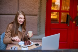 Cheerful girl sitting in a cafe, eating a chocolate dessert and drinking a coffee drink, and smiling. Outside.