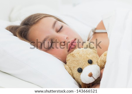 Cheerful girl sleeping with her teddy bear in her bed