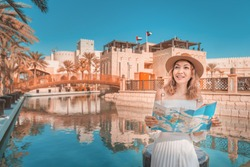 Cheerful girl standing with map near Madinat Jumeirah Hotel and Mall. Travel and tourism in Dubai and United Arab Emirates