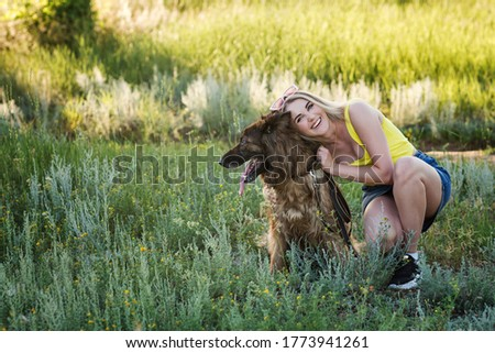 Cheerful girl walks with her dog. Young woman hugging German Shepherd dog on lawn. Soft focus