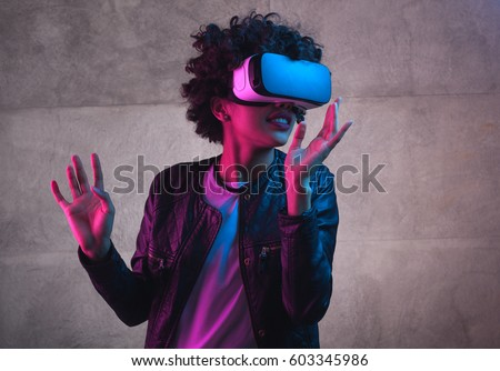 Cheerful girl with hands up wearing the virtual reality goggles.