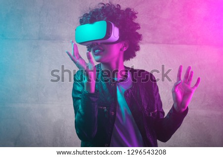 Cheerful girl with hands up wearing the virtual reality goggles. Cyan and magenta colors