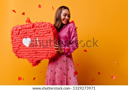 Cheerful girl with pretty smile posing with red bunner. Studio shot of refined brunette female blogger in good mood.