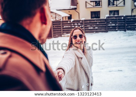 Cheerful girlfriend. Cheerful girlfriend feeling joyful while taking her man for a walk in the park #1323123413